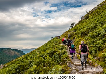 Ben Nevis / UK - August 24 2019: People hike on 'Mountain Path', the most popular route up Ben Nevis, in the Scottish Highlands.