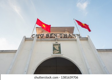Ben Thanh Market (built in 1912-1914), the facade and the arch of the central entrance and two swaying Vietnamese flags. The market is one of the top attractions of Ho Chi Minh City (Saigon), Vietnam.