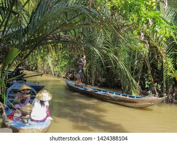 Ben Tre, Vietnam, January 3, 2015. Two Vietnamese women have lunch sitting in a wooden boat. Standing on another boat and driving a paddle, a man moves along the river.