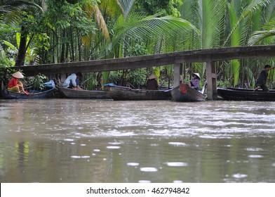 Ben Tre, Vietnam - June, 17, 2015: Boatman shelt from the rain under the bridge in Ben Tre, Vietnam.