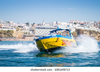 Benagil, Portugal - September 11, 2016: Speed boat or jet boat ride and dolphin watching experience by the coasts of Albufeira. or jet boat ride dolphin watching experience by the coasts of Albufeira.