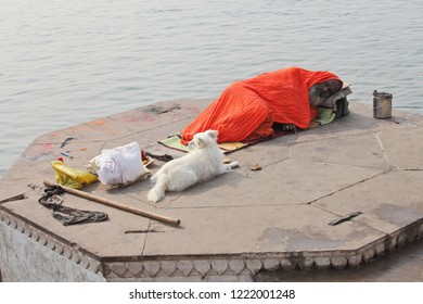 BENARES, UTTAR PRADESH, INDIA - FEBRUARY 13, 2013: Hindu sadhu is sleeping on ghat of the Ganges river