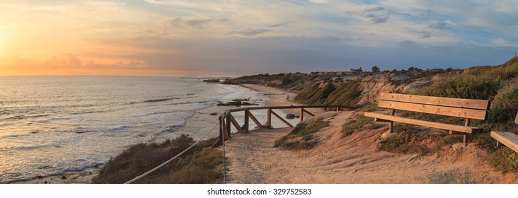 Bench along an outlook with a view of Crystal Cove Beach, Newport Beach and Laguna Beach line in Southern California