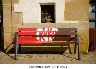 Bench along a street decorated by local company with KitKat advertising making it good to sit on.  Arre, Spain. June 12, 2019