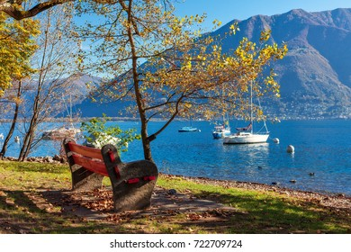 Bench among colorful autumnal trees, yachts on Lake Maggiore and mountains in town of Locarno, Switzerland.