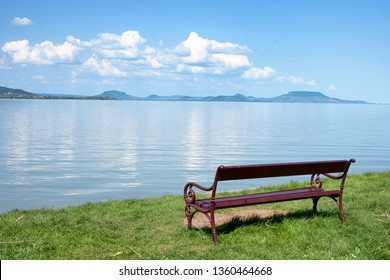 Bench at the beach of lake Balaton with the Badacsony mountains in the background in Hungary