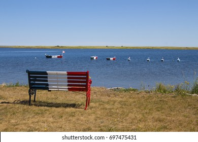 Bench and boats with French Acadian flag in Bouctouche, New Brunswick, in the Maritimes, Atlantic Canada on a sunny day