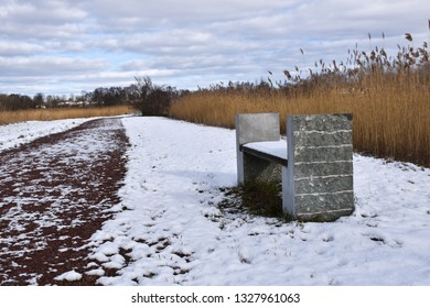 Bench by a footpath in the reeds in winter season at the swedish island Oland