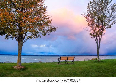 A bench and colorful skies over Traverse Bay in early morning at Elk Rapids, Michigan, USA