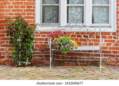 Bench with flowers and pumpkins at old brick house in Luneburg. Germany
