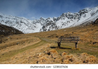 Bench in front of beautyful mountains in Winter in front of a blue cloudy sky in Valle di Viso