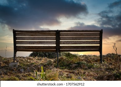 A bench in front of a sunset