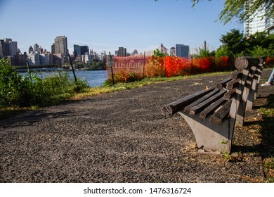 A bench at Gantry Plaza State Park next to the east river and a cityscape of Manhattan, New York