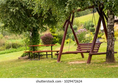 a bench hanging beetwen trees.