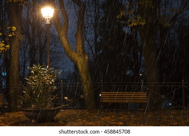 bench illuminated by a streetlight at night in the rain