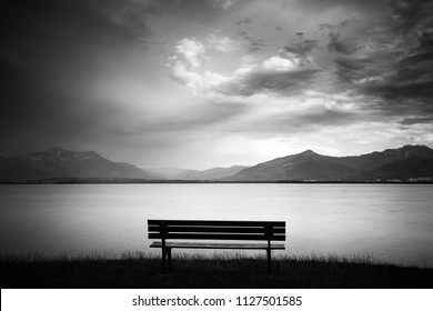 Bench at lake Chiemsee with view to the alps