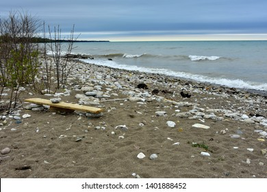 A bench made of driftwood along the shoreline of one of the Great Lakes with crashing waves and stormy skies in the background.