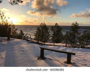 Bench near the Baltic sea in winter sunset