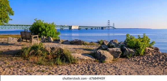 A bench on the beach in late morning overlooking the Straits of Mackinac and the Mackinaw Bridge connecting Michigan's upper and lower peninsulas, USA