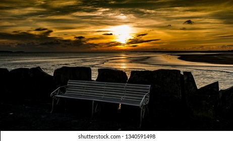 The bench on Burry Port breakwater Carmarthenshire. Wales. UK.  Sunset in the distance.