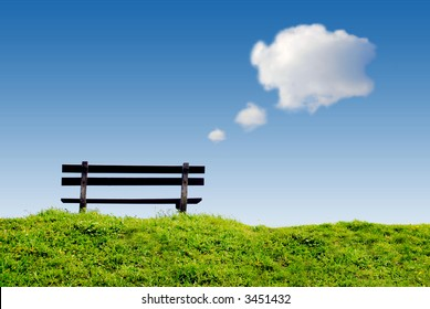bench on green grass with conceptual text-balloon thinking and day dreaming clouds in clear blue sky