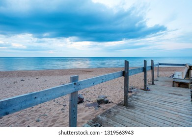 Bench on the Inverness beach at sunset, Nova Scotia, Canada