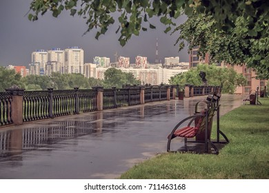 Bench on promenade of rive in Kemerovo downtown after summer rain Siberia. Russia