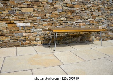 Bench on a stone terrace in front of stone wall