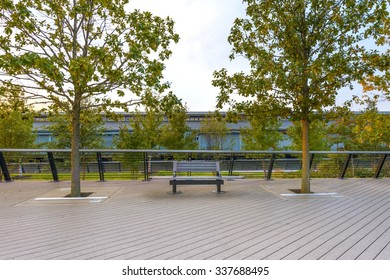 bench on tree lined Ben Franklin Bridge public walkway and building with loading bays across the river
