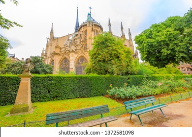 bench in park of Notre Dame de Paris, popular landmark and cathedral of the capital city of France. Gothic French architecture of Our Lady of Paris in a sunny day, blue sky.