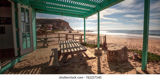 Bench and picnic table at Crystal Cove State Park beach, right on the sand with an ocean view in Newport Beach, California