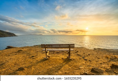 Bench in Populonia famous cliff Buca delle Fate at sunset. Elba Island on the horizon. Piombino, Maremma Tuscany, Italy.