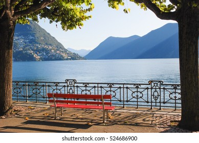 The bench at the promenade of the luxurious resort in Lugano on Lake Lugano and Alps mountains in Ticino canton of Switzerland.