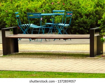 Bench in public park with tables behind them.