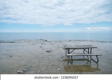 A bench at a rocky beach of Georgian Bay