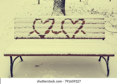 Bench in the snow with a pair of Valentine hearts