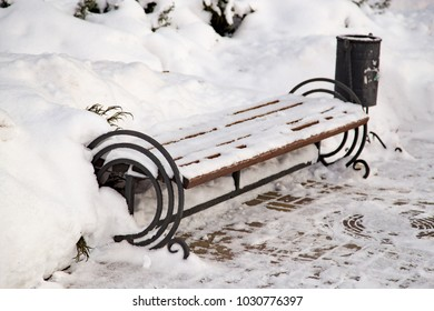 A bench in the snow in the park