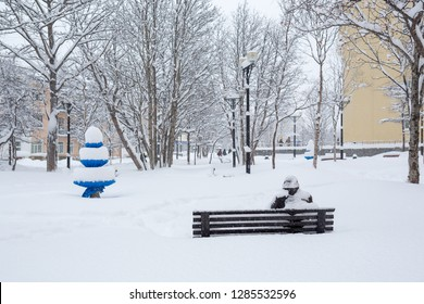 Bench in a snowy city square. After the snowfall there is a lot of snow on the branches of trees and large snowdrifts. Cold winter weather. Feeling of loneliness. Magadan, Siberia, Far East of Russia.