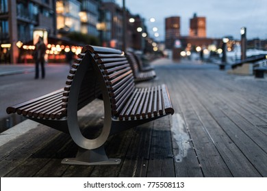 Bench in the sunset on Aker Brygge in Oslo, Norway. In the back you can see the city hall. Aker Brygge is a popular tourist attraction in this European town. This part of Oslo represents the new Oslo