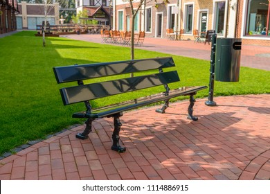 Bench and trash can on a city street. Summer rest