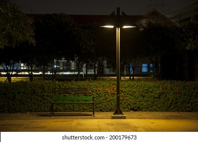 Bench under lamp In a park during the night.