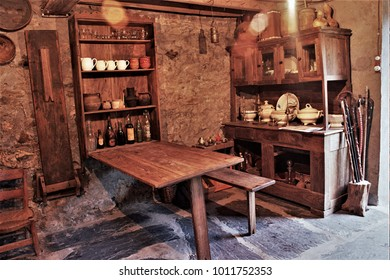 benches and folding tables of old wood in rural house of Galicia, old country kitchen with hanging pans, kitchen of a rural house in Galicia, old wooden furniture,  typical rural cuisine of Galicia,