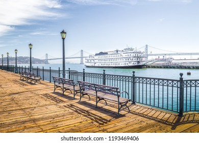 Benches at historic Pier 7 with traditional paddleboat and Oakland Bay Bridge in the background on a sunny day with bliue sky and clouds, San Francisco, California, USA
