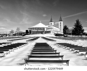 Benches in Medjugorje covered with snow, behind the church