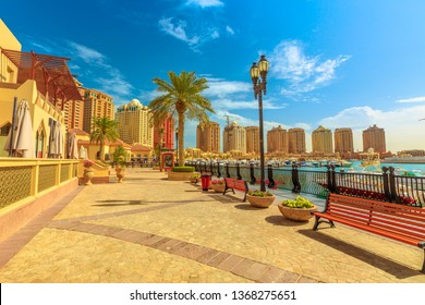 Benches and palm trees along marina walkway promenade in Porto Arabia at the Pearl-Qatar, Doha, with residential buildings towers on background. Persian Gulf in Middle East. Sunny day, blue sky.