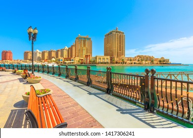 Benches and palm trees along marina walkway promenade in Porto Arabia at the Pearl-Qatar, Doha, with residential towers and luxury boats on background. Persian Gulf in Middle East. Sunny day.