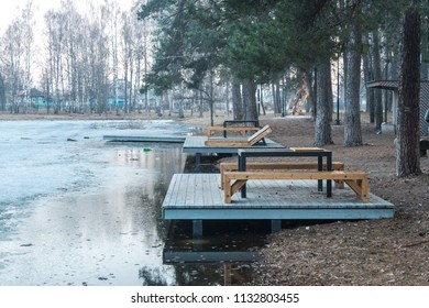 Benches, tables and sunbeds in the spring near the frozen lake