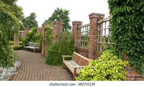 Benches in a walled garden with mono-block path and red brick pillars