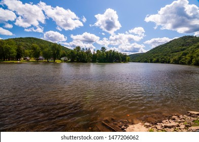 A bend in the Allegheny river in Warren county, Pennsylvania, USA on a sunny summer day with a bright blue skies and white clouds