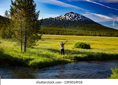 Bend, Oregon - 7/6/2016:  A young man offering praise to Mt Bachelor, looking accross Sparks Meadow in the Oregon cascade mountains on century drive near Bend, Oregon